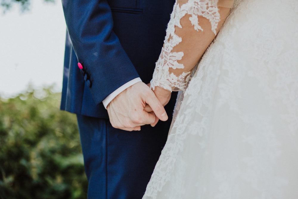sposi che si tengono per mano il giorno del matrimonio
